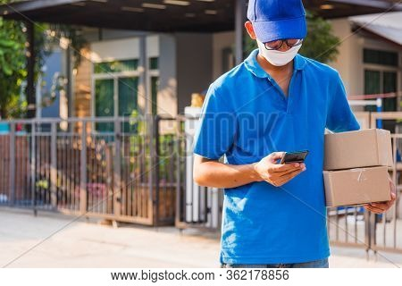 Asian Delivery Man Courier Online Holding Deliveries Out Boxes And Using Mobile Phone Contact The Cu