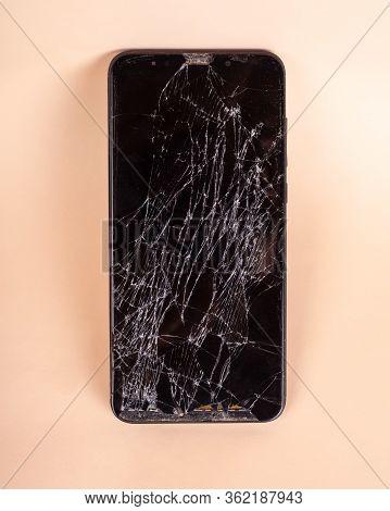 Broken Touchscreen Black Phone, Smartphone, Broken Glass Display Smartphone On A Beige Background .