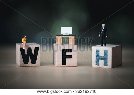 Miniature People Sit On Wood Blocks Of Wfh With Miniature Office Table. Concept Of Work From Home
