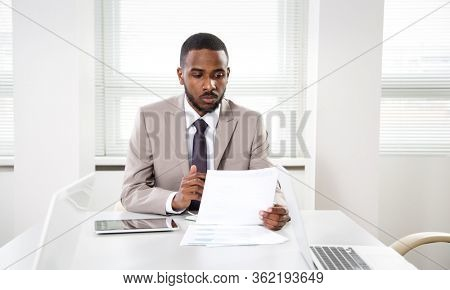 Young handsome african american businessman working alone in the office