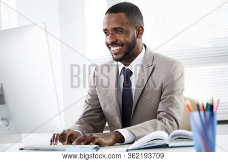 Happy young handsome african american businessman working alone in the office