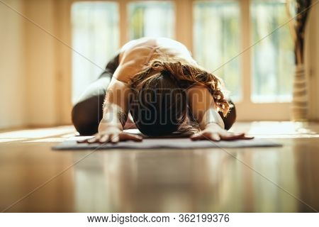 Young Woman Is Doing Yoga Meditation In The Living Room At Home. She Is Meditating On Floor Mat In M