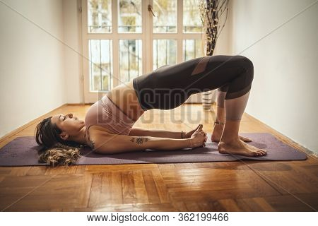 Young Woman Is Relaxing During Corona Virus Pandemic Doing Yoga Meditation In The Living Room At Hom