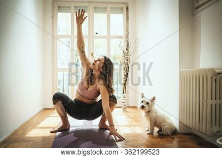 Young Woman Is Doing Yoga Meditation During Corona Virus Pandemic In The Living Room At Home. She Is