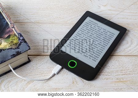 E-reader Connected By Cable To A Paper Book On A White Wooden Table. Copy Space On E-book Display. E