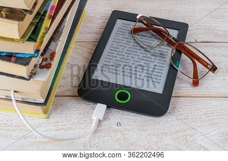 Vision Glasses On E-book Reader Connected By Cable To Stack Of Paper Books On A White Wooden Table.