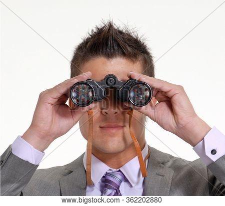man looks a coronavirus arriving from long distance using a binoculars