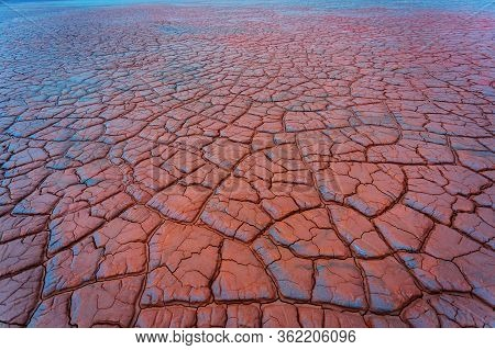 Abstract red and blue ground background. Dry and cracked ground land. Salt polluted soil. Global warming and climate change. Environmental pollution by chemical waste. Ecological catastrophe