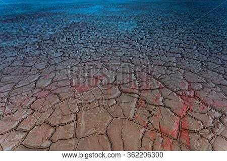 Dry and cracked ground land. Salt polluted soil. Global warming and climate change. Abstract red and blue ground background. Environmental pollution by chemical waste. Ecological catastrophe