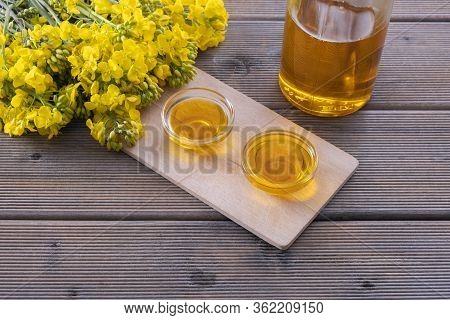 A Bottle Of Rapeseed Oil And Cups Of Rapeseed Oil Are On The Table, Next To Young Rapeseed Flowers O
