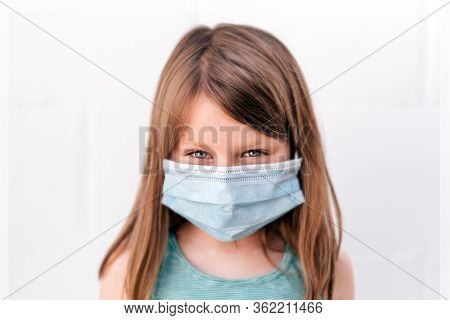 Portrait Of A Girl With Blue Eyes Wearing An Anti-virus Mask With Intense Assertive Positive Gaze Lo