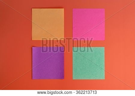 Colored Square Leaflets For Reminders Top View. Reminder Sticky Note On Red Background, Empty Space