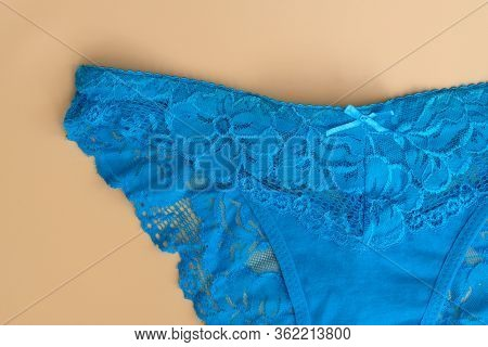 Blue Female Panties Fragment Top View.  Openwork Panties On A Beige Background. Lingerie With Lace.