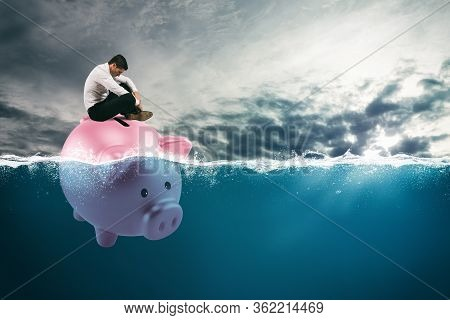 Business Man In Financial Trouble Sails On Piggy Bank In Bad Waters Due To The Crisis