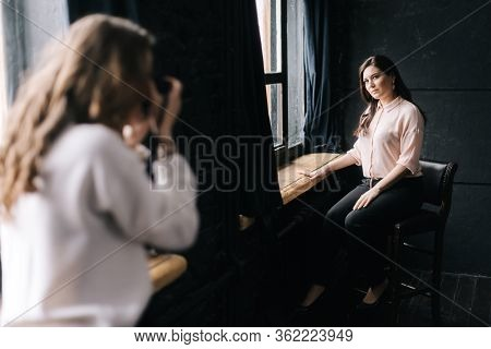 Woman Model Posing While Sitting On Chair In Photo Studio For Unrecognizable Female Photographer Whi