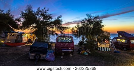 Campers And Motorhomes Overlooking Sunset In The Mediterranean Sea From Their Campsite On The Beach,