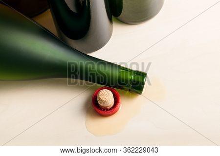 Top View Of Overturned Cognac Bottle In Spilled Liquid Near Empty Wine Bottles On Wooden Board