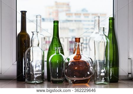 Different Empty Bottles On Windowsill And View Of City Through Home Window On Background