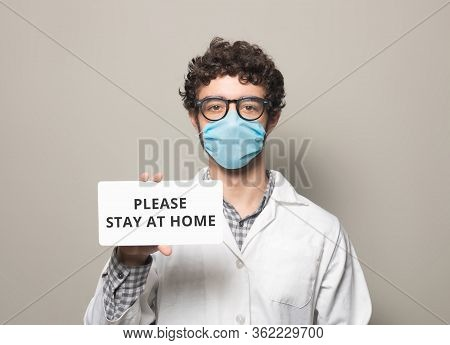 Doctor With Face Mask Holding A Sign With Text Please Say At Home