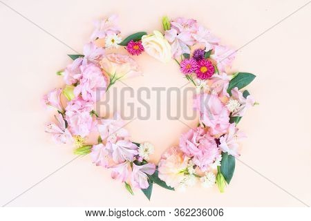 Flowers Composition. Round Frame Made Of Eustoma, Lilly And Daisy Flowers On Pink Background. Flat L