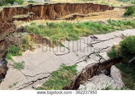 The Sunk Asphalt Road After A Landslide, Natural Disaster Landslide Of Soil With An Asphalt Road Wit