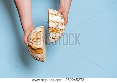 Top View Of Sourdough Bread Cut In Two, Held In The Hands Of An Unrecognizable Woman. Healthy Food H