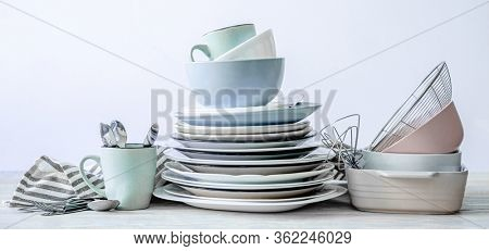 Top view on clean kitchenware and dishcloth on white table