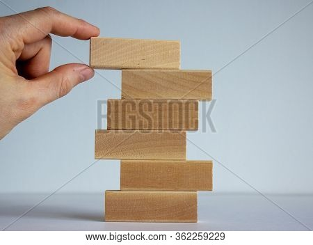 Concept Of Building Success Foundation. Women Hand Put Wooden Blocks On The Stack Of Wooden Blocks.