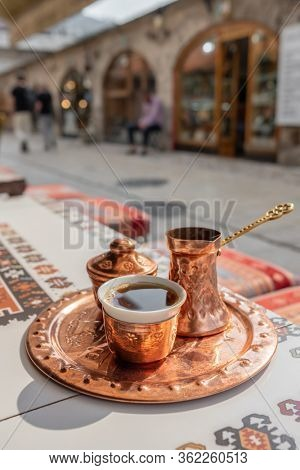 Traditional black bosnian coffee in beautiful copper cezve on the table in old town of Sarajevo, BiH A complete Bosnian coffee set is called a kahveni takum