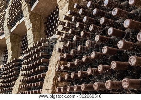 Wine bottles covered with spider web stacked up in old wine cellar . Underground wine cellars