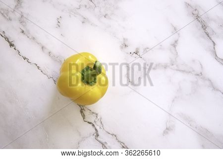 One Yellow Bell Pepper On A White Marble Background