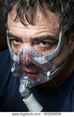 Coronavirus patient man in oxygen mask close-up face