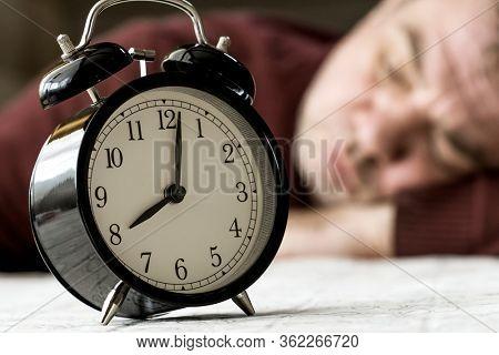 A man sleeps at a table, an alarm clock near him