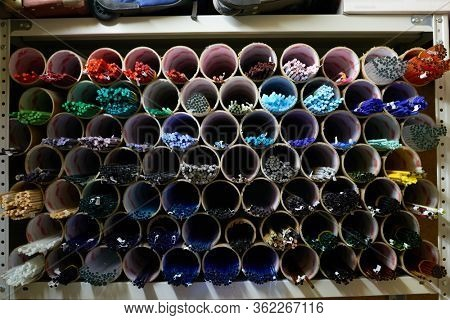 Several rows of pipeshaped shelves with multi-color workpieces for lampworking inside workshop of contemporary craftsperson