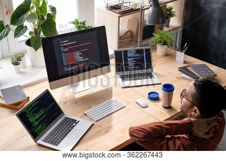 Above view of puzzled middle-eastern programmer in glasses sitting in front of computers and analyzing web script