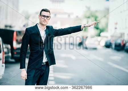 Portrait of a goodlooking young man catching a taxi in the street of a big city. Young businessman. Men's beauty, fashion.