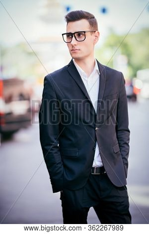 Portrait of a goodlooking young man walking along the street of a big city. Young businessman. Men's beauty, fashion.