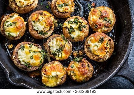 Baked champignons mushrooms, filled with cheese, parsley and roasted garlic in black bowl. Selective focus. Healthy food concept.