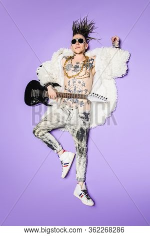 A full length portrait of a cool young punk man posing in the studio. Casual punk fashion, beauty.
