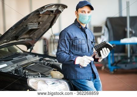 Masked car mechanic holding a jug of motor oil during coronavirus pandemic