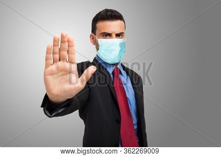 Masked businessman showing the stop sign, coronavirus pandemic social isolation, business halt and stay at home concepts