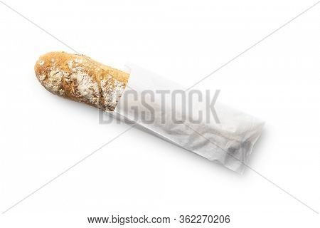 Fresh whole grain bread baguette in paper bag isolated on white background.