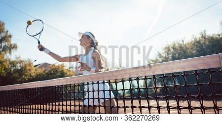 Woman getting a ball close to net on the tennis court