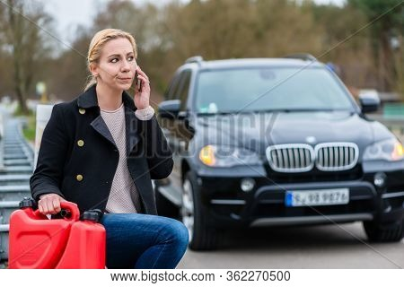 Woman has car with empty gas tank calling for help on phone holding spare canister in hand