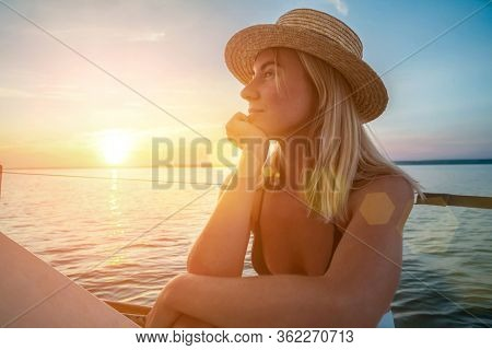 Young happy woman enjoying sunset from deck of sailing boat moving in sea at evening time. Travel, Summer, Holidays, Journey, Trip, Lifestyle,