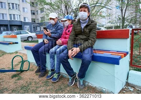 father and children sitting on a bench on playground near high-rise buildings with apartments, a medical mask on their faces protects against viruses and dust