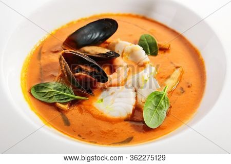 Bouillabaisse in white bowl. Served main course close up. French seafood, soup with fish and mussels. Restaurant food portion, main course. France cuisine. Dinner, gourmet meal in plate