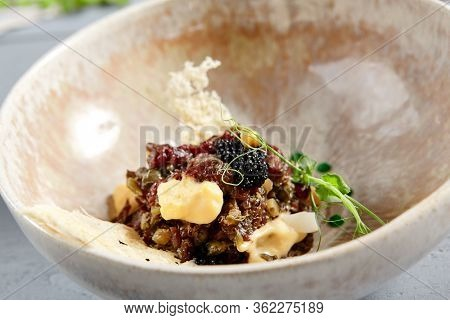 Beef tartar in beige ceramic bowl. Meat appetizer with pike caviar and hollandaise sauce close up. Raw snack, american and european cuisine meal. Served restaurant menu food, delicatessen