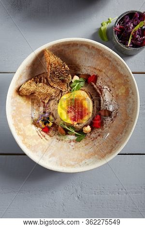 Rabbit liver pate with peach, honey and nuts in beige bowl. Dietary appetizer close up. Dietetic snack with peas twigs and violet flowers decoration. Served delicatessen, restaurant menu food