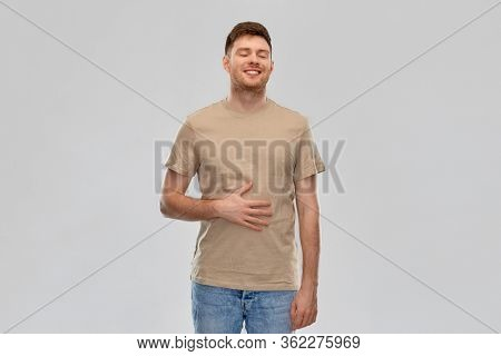 digestion, satisfaction and people concept - happy smiling full man touching his tummy over gray background